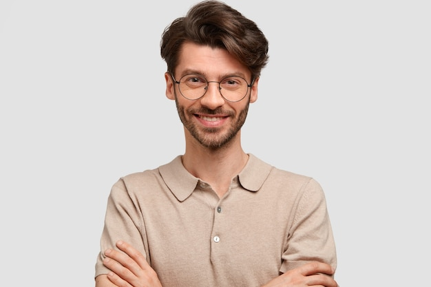 Portret van gelukkig opgetogen aantrekkelijke man houdt de handen gekruist, gekleed in casual outfit, kijkt vreugdevol, zelfverzekerd in succes, geïsoleerd over witte muur