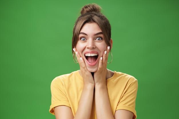 Portret van gelukkig opgetogen en verrast jong vrouwelijk meisje in geel t-shirt