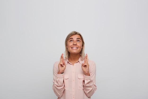 Portret van gelukkig opgewonden blonde jonge vrouw met beugels aan tanden draagt roze shirt houdt vingers gekruist, kijkt op en doet een wens geïsoleerd over witte muur