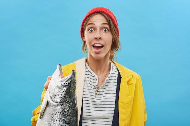 Portret van gelukkig opgewonden jong wijfje dat zich bij lege blauwe muur bevindt, grote zoetwatervis vasthoudt, zich vrolijk en verbaasd voelt. mensen, hobby, activiteit, vrije tijd en recreatieconcept