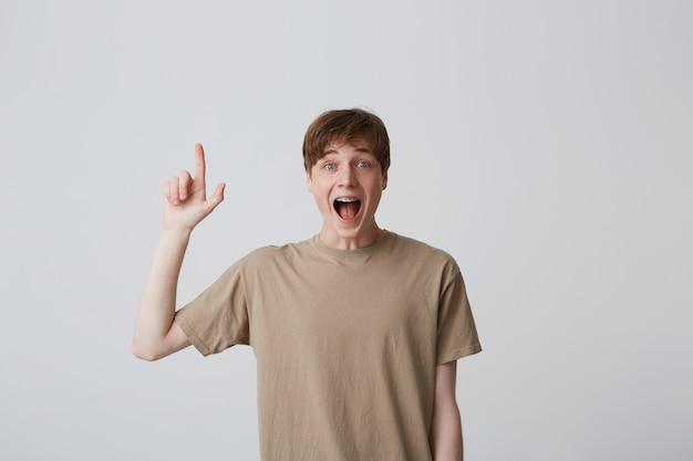 Portret van gelukkig opgewonden jonge man met kort kapsel