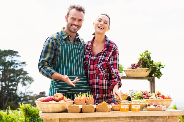Portret van gelukkig paar dat organische groenten verkoopt