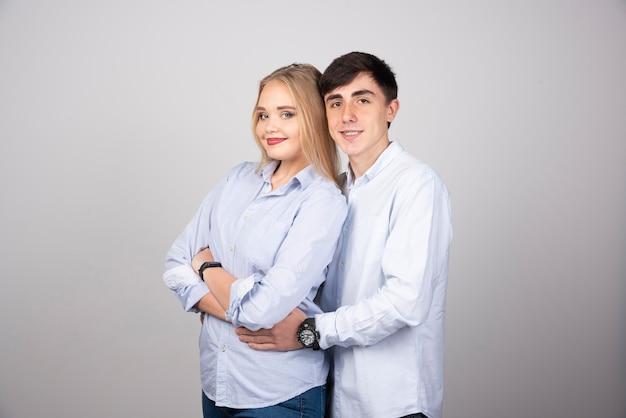 Portret van gelukkig paar dat tegen grijze muur kijkt.