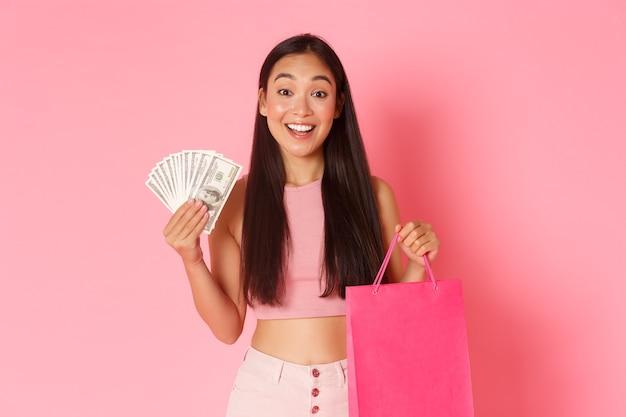 Portret van gelukkig prachtig aziatisch meisje heeft genoeg geld om te kopen wat ze wil, met contant geld en boodschappentas, staande over roze muur, concept van speciale kortingen en promo's