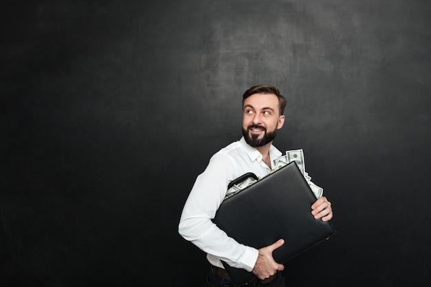 Portret van gelukkig rijk zakenman dragend aktentashoogtepunt van dollarrekeningen en terug kijkend, geïsoleerd over donkergrijs