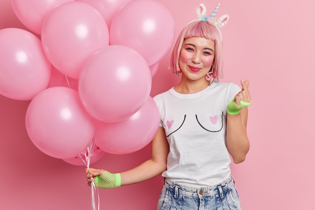 Portret van gelukkig roze harige vrouw met oosterse verschijning gebaren mini teken gebaar poses met helium ballonnen geniet van vakantie gekleed in modieuze kleding