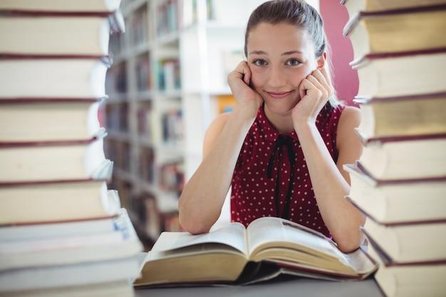 Portret van gelukkig schoolmeisje die bibliotheek bestuderen