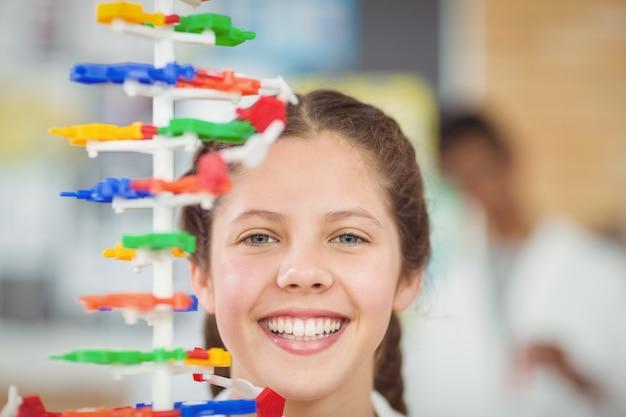 Portret van gelukkig schoolmeisje experimenteren molecuul model in laboratorium