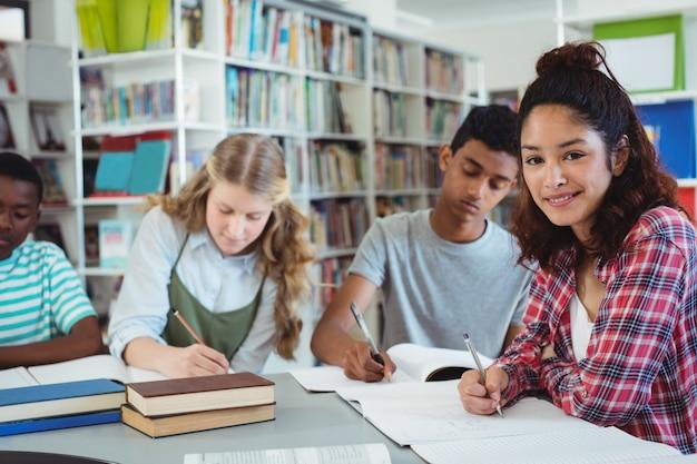 Portret van gelukkig schoolmeisje studeren met haar klasgenoten in bibliotheek Premium Foto