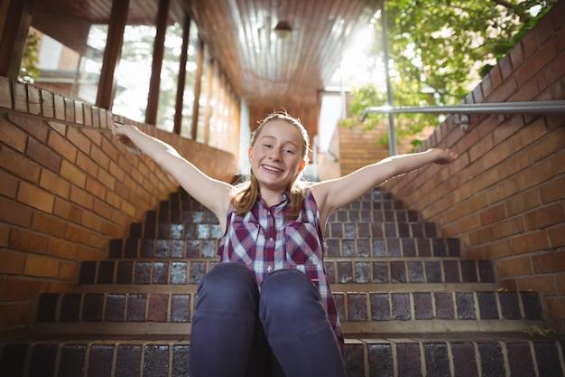 Portret van gelukkig schoolmeisje zitten met uitgestrekte armen op de trap