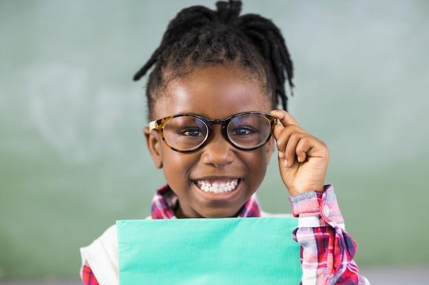 Portret van gelukkig schoolmeisjebedrijfsdossier in klaslokaal