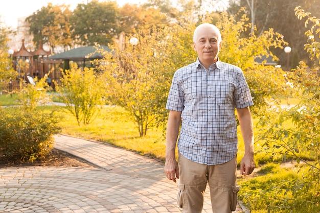Portret van gelukkig senior man poseren in voorjaar park