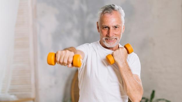 Portret van gelukkig senior man tillen gewichten