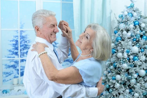 Portret van gelukkig senior paar op kerstmis thuis dansen