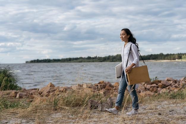 Portret van gelukkig succesvolle schilder wandelen langs het strand, op zoek naar inspiratie
