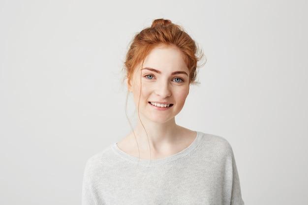 Portret van gelukkig teder gembermeisje met het blauwe ogen en sproeten glimlachen.