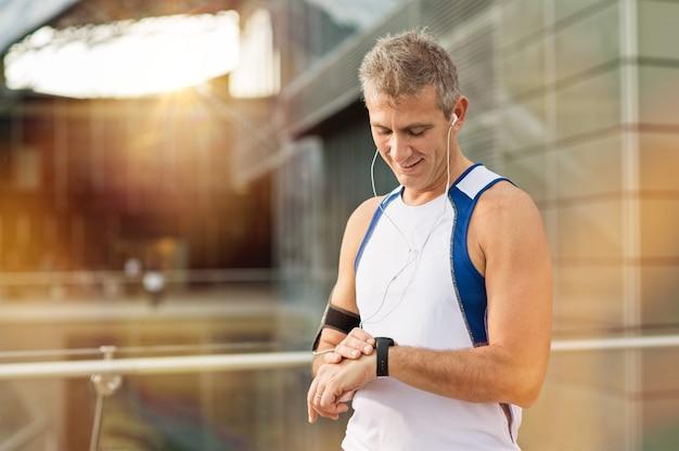Portret van gelukkig volwassen man met hartslagmeter op pols