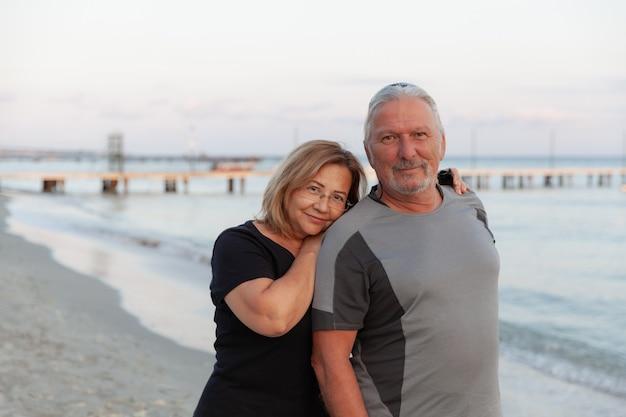 Portret van gelukkig volwassen man wordt omarmd door zijn vrouw op het strand