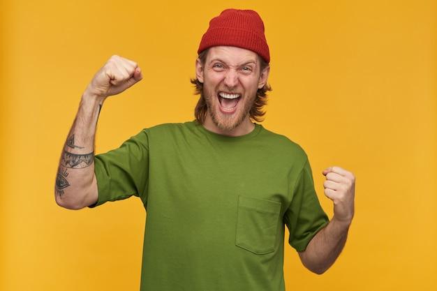 Portret van gelukkig, volwassen mannetje met blond kapsel en baard. het dragen van een groen t-shirt en een rode muts. heeft tatoeages. heft vuist op. vier de overwinning. geïsoleerd over gele muur