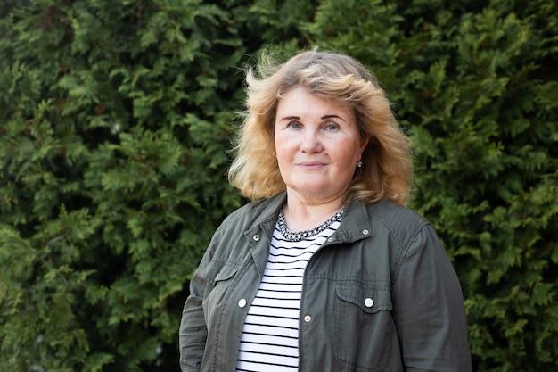 Portret van gelukkig volwassen vrouw in de tuin