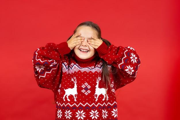 Portret van gelukkig vrolijk charmant meisje in rode kersttrui met rendieren die ogen bedekken met p...