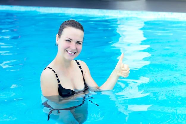 Portret van gelukkig vrolijk meisje, zwemmer, positieve jonge vrouw. dame staat, geniet in zwembad.