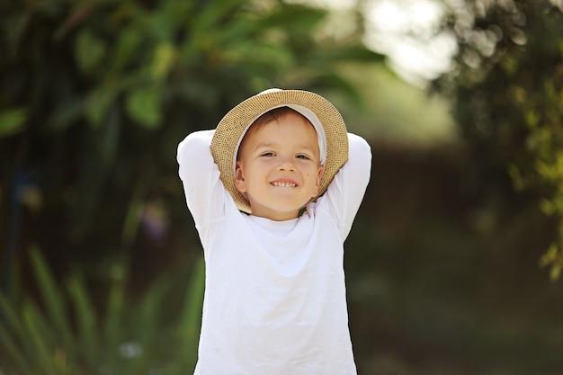Portret van gelukkig vrolijke mooie kleine jongen in wit overhemd en stro hoed geïsoleerd op natuurlijke wazig tuin achtergrond.