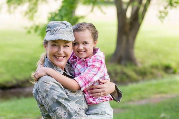 Portret van gelukkig vrouwelijke soldaat met haar dochter in park