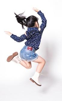 Portret van gelukkig weinig aziatisch kind springen geïsoleerd op witte achtergrond Premium Foto