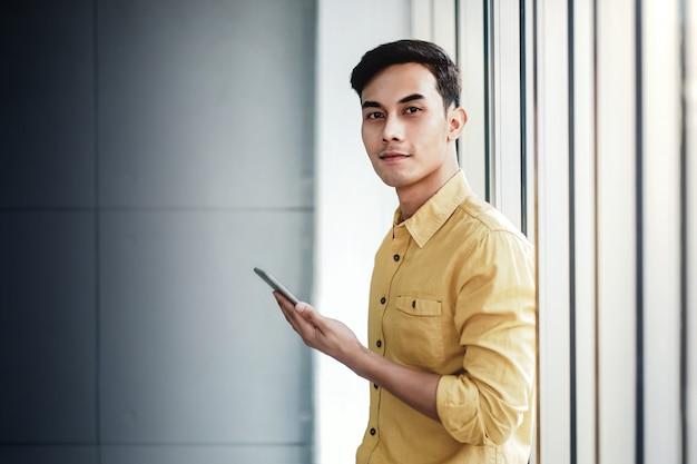Portret van gelukkig zakenman permanent door het raam in office