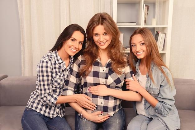 Portret van gelukkig zwanger meisje, zittend op de bank met haar vriendinnen