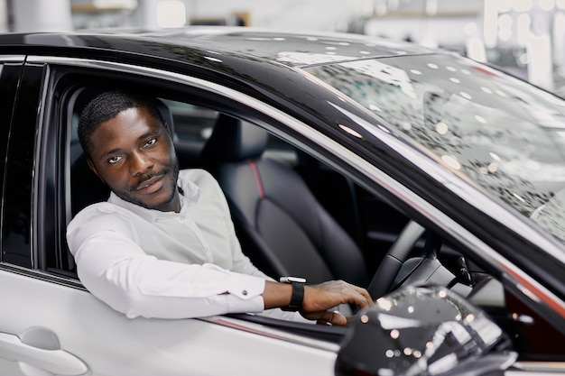 Portret van gelukkig zwarte zakenman binnenkant van luxe auto