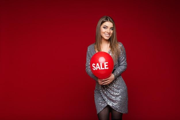 Portret van gelukkige aantrekkelijke dame die en rode ballon met een inscriptieverkoop houdt.