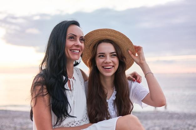 Portret van gelukkige aantrekkelijke glimlachende dochter met moeder knuffelen en samen plezier hebben in de zomer bij zonsondergang aan zee