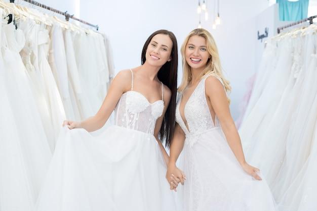 Portret van gelukkige aantrekkelijke jonge bruiden in stijlvolle trouwjurken staan in de showroom