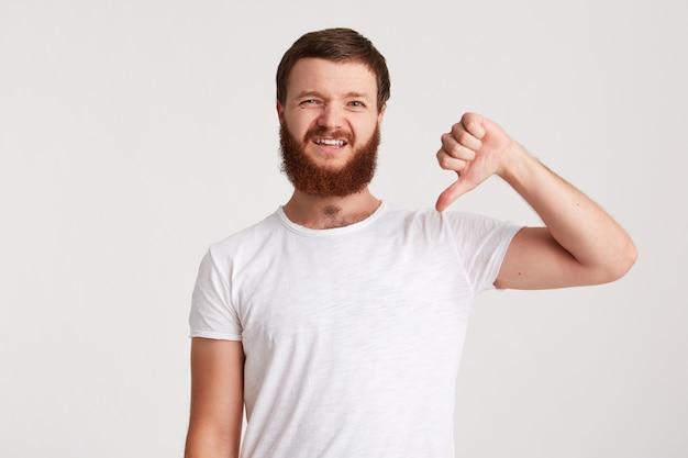 Portret van gelukkige aantrekkelijke jonge man hipster met baard draagt t-shirt ziet er zelfverzekerd uit en wijst naar de zijkant op copyspace met vinger geïsoleerd over witte muur