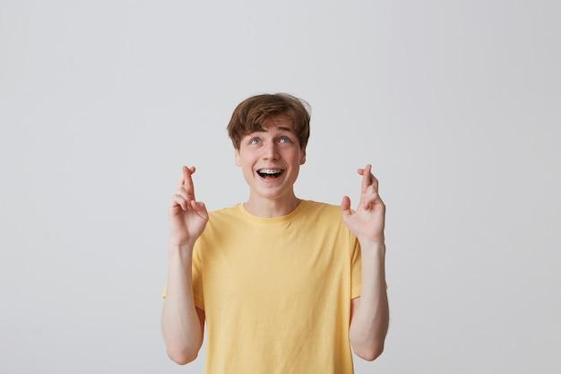 Portret van gelukkige aantrekkelijke jonge man met beugels aan de tanden in gele t-shirt