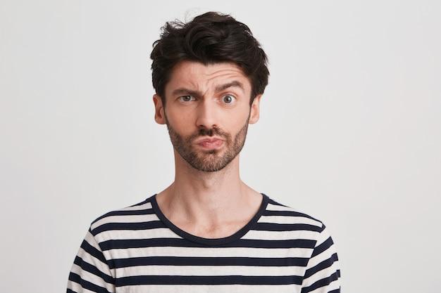 Portret van gelukkige aantrekkelijke jonge man met borstelharen draagt een gestreepte t-shirt voelt opgewonden en glimlachend geïsoleerd op wit
