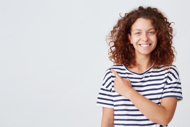 Portret van gelukkige aantrekkelijke jonge vrouw met krullend haar draagt gestreepte t-shirt