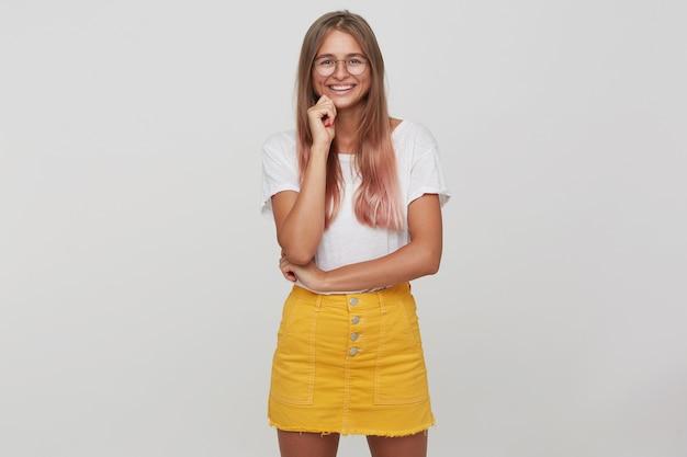 Portret van gelukkige aantrekkelijke jonge vrouw met lang geverfd pastelroze haar draagt t-shirt, gele rok en bril staan, ziet er zelfverzekerd uit en glimlacht geïsoleerd over witte muur