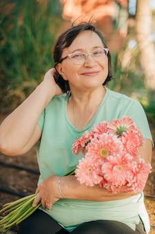 Portret van gelukkige aantrekkelijke volwassen vrouw buitenshuis