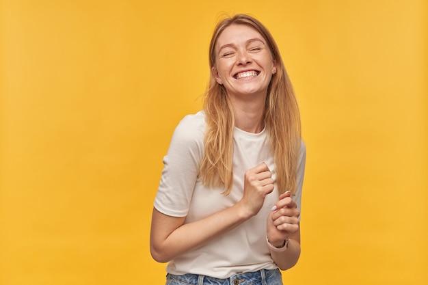 Portret van gelukkige aantrekkelijke vrouw met sproeten in witte t-shirt lachen, dansen voelt ontspannen en plezier maken op geel