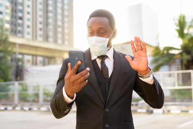Portret van gelukkige afrikaanse zakenman met masker videobellen in de stadsstraten