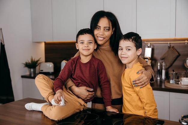 Portret van gelukkige afro-amerikaanse familie in de keuken, moeder en twee zonen kijken naar de camera. hoge kwaliteit foto