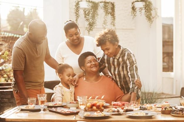 Portret van gelukkige afro-amerikaanse grootmoeder die verjaardag viert met familie tijdens het diner buiten...