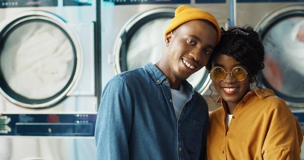 Portret van gelukkige afro-amerikaanse vrolijke paar verliefd knuffelen en glimlachen naar de camera in de wasservice. blije jonge man en vrouw die zich bij werkende wasmachines binnen washuis bevinden.
