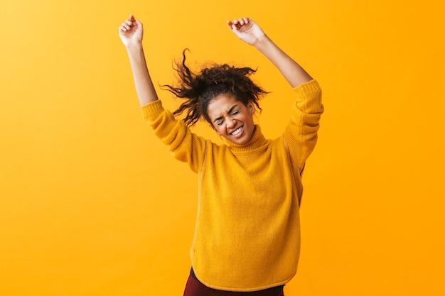 Portret van gelukkige afro-amerikaanse vrouw met afro kapsel vreugde en dansen, geïsoleerd
