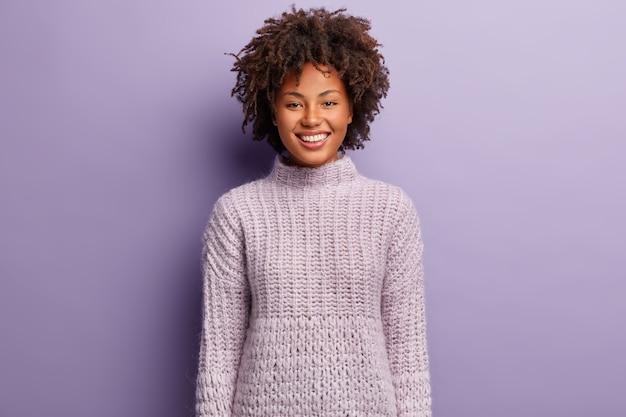 Portret van gelukkige afro-amerikaanse vrouw met krullend haar, heeft een gezonde huid, draagt gebreide paarse trui, vormt binnen, lacht om iets grappigs. monochroom. mensen en positiviteit