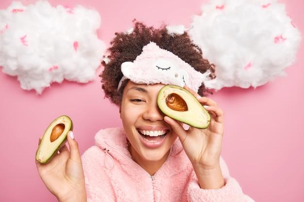 Portret van gelukkige afro-amerikaanse vrouw vormt binnen met avocado dekt ogen glimlacht in grote lijnen toont witte tanden heeft goed verzorgd gezonde huid gekleed in nachtkleding voelt ontspannen ontspannen na slaap