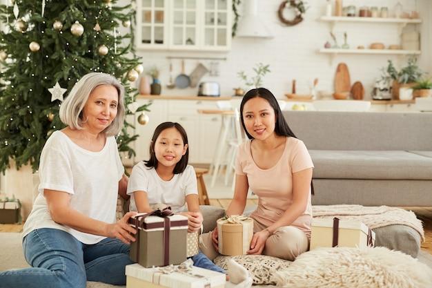 Portret van gelukkige aziatische familie lachend zittend op de vloer met kerstcadeautjes in de woonkamer